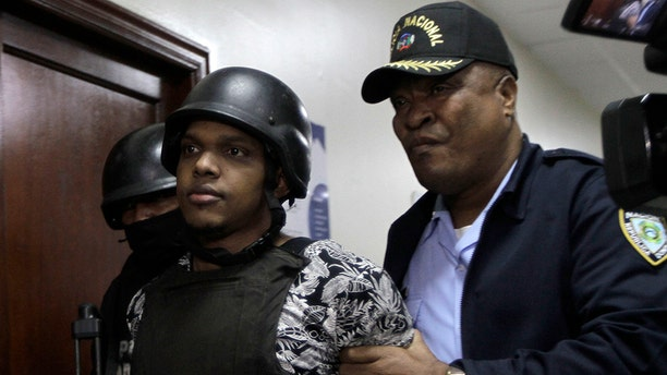 José Eduardo Ciprian, a suspect in connection with the shooting of former Boston Red Sox slugger David Ortiz, is taken to court by police in Santo Domingo, Dominican Republic, Friday, June 14, 2019. Ortiz was shot in the back at a bar in the Dominican Republic on Sunday, June 9. (AP Photo/Roberto Guzman)