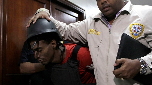 Joel Rodríguez Cruz, a suspect in connection with the shooting of former Boston Red Sox slugger David Ortiz, is taken to court by police in Santo Domingo, Dominican Republic, Friday, June 14, 2019. Ortiz was shot in the back at a bar in the Dominican Republic on Sunday, June 9. (AP Photo/Roberto Guzman)