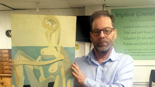 Andrew Potter, auctioneer and owner of Brighton and Hove Auction House with the suspected Picasso painting. (Credit: SWNS)
