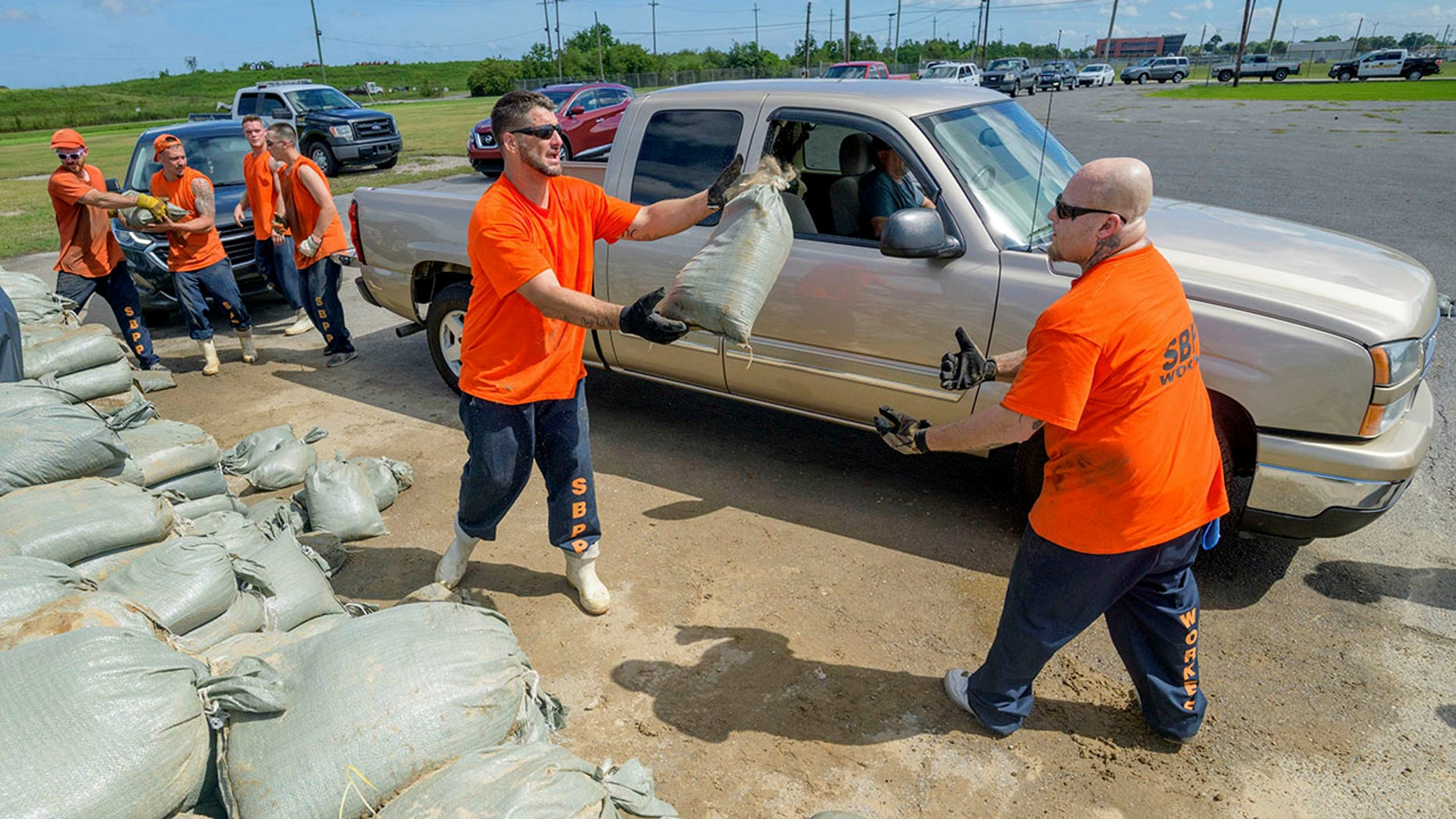 Employees at the St. Bernard Parish Sheriff's Office move free sandbags to residents of Chalmette, Louisiana on Thursday, July 11, 2019, in front of Tropical Storm Barry in the Gulf of Mexico. (AP Photo / Matthew Hinton)