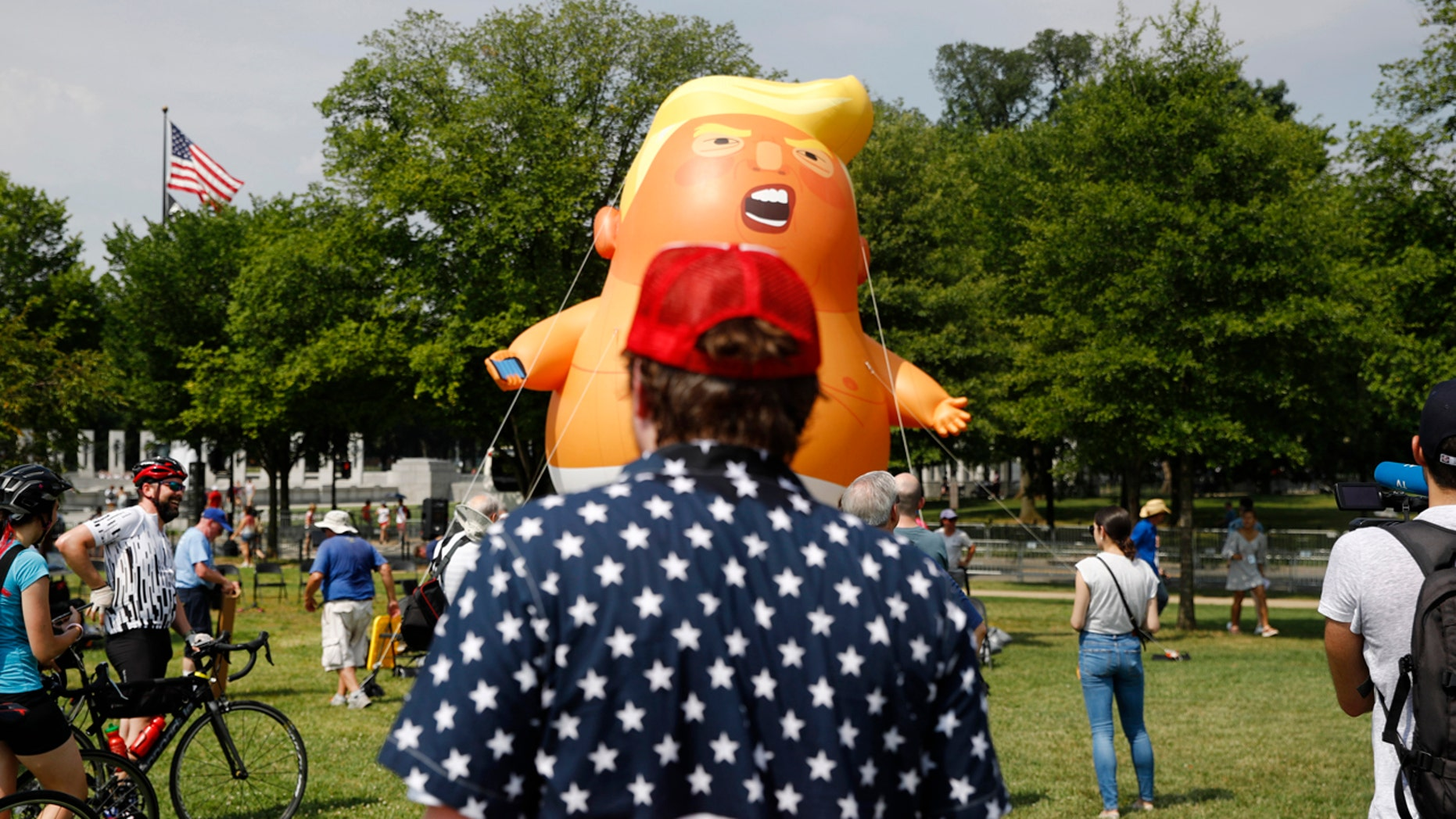"A man who gave his name only as ""Schwartz,"" foreground, of Greensboro, N.C., views a Baby Trump balloon as it is moved into position before Independence Day celebrations on the National Mall in Washington. (AP Photo/Patrick Semansky)"