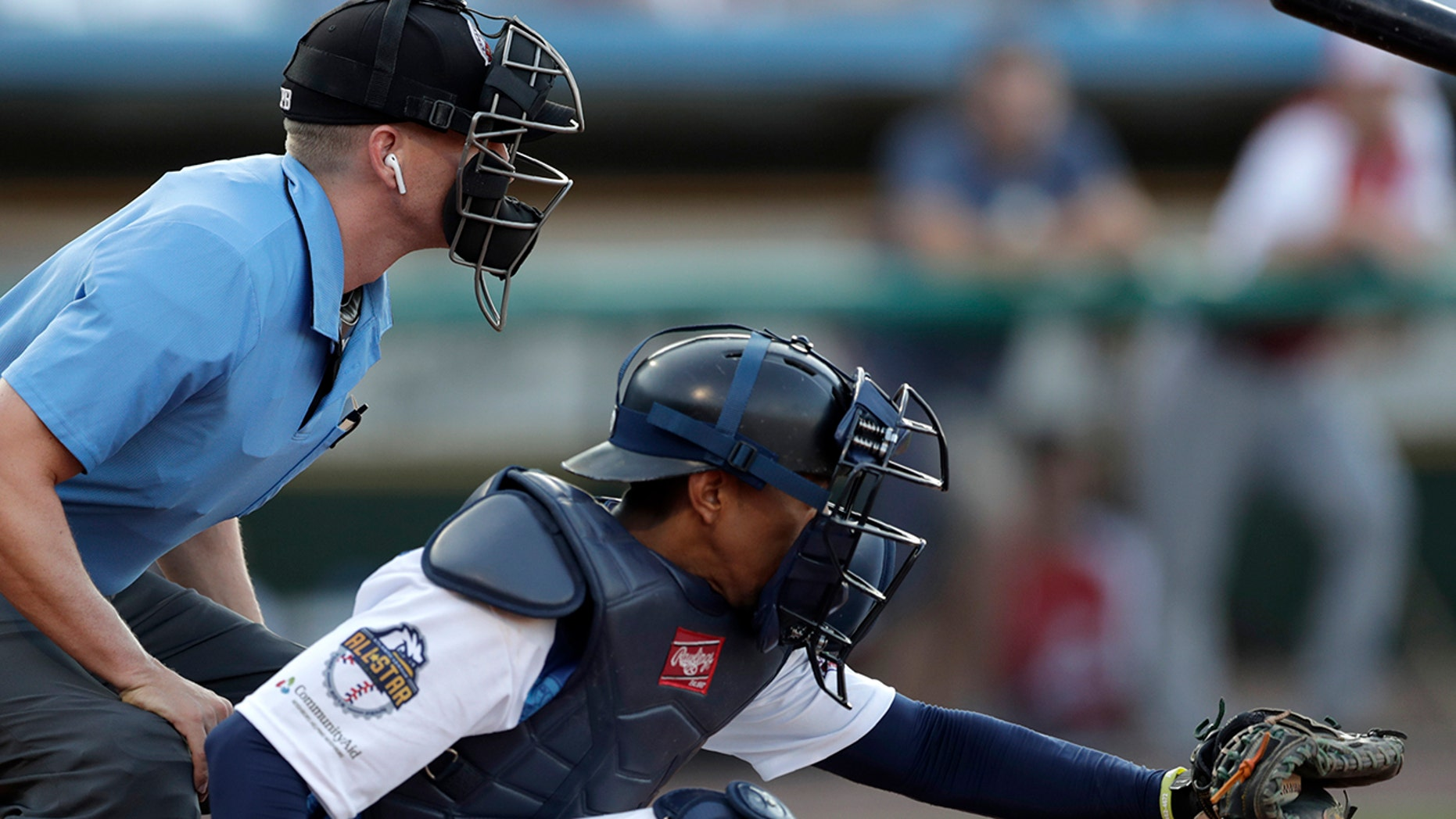 Home plate umpire Brian deBrauwere, left, huddles behind Freedom Division catcher James Skelton, of the York Revolution, as the official wears an earpiece during the first inning of the Atlantic League All-Star minor league baseball game, Wednesday, July 10, 2019, in York, Pa. (AP Photo/Julio Cortez)
