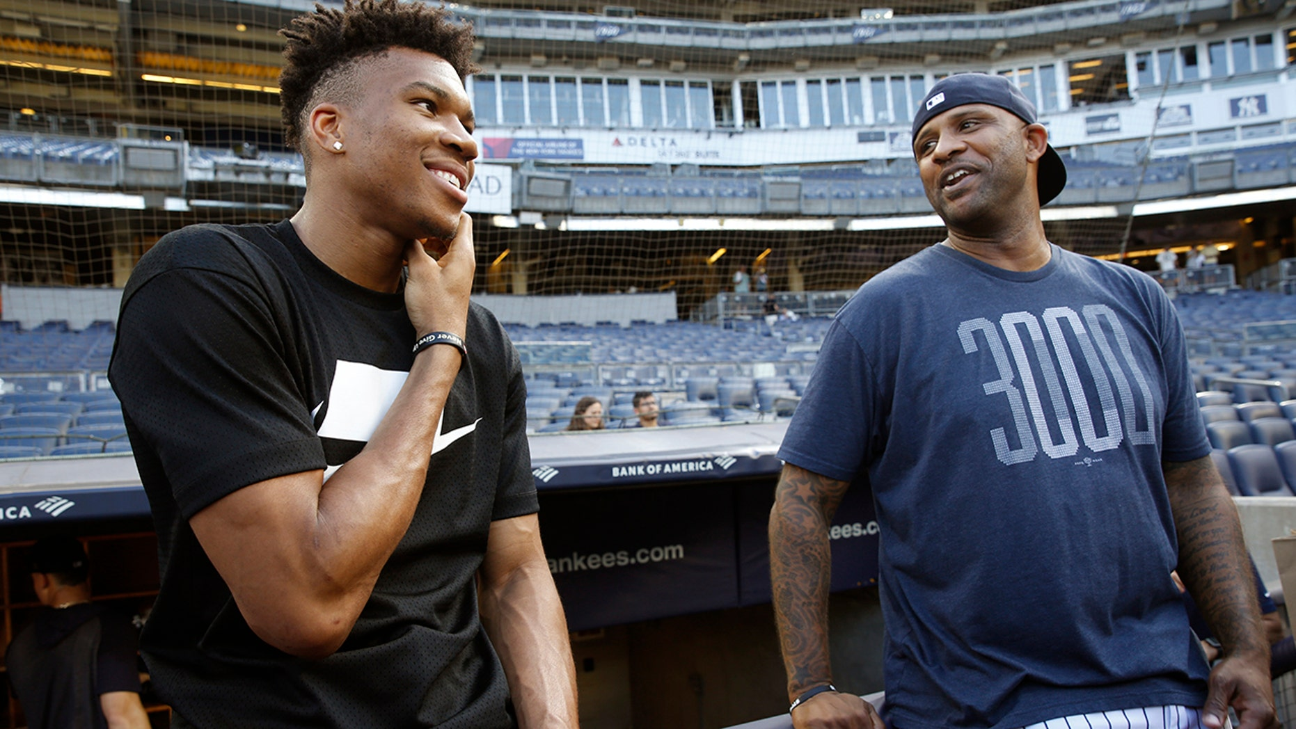 Milwaukee Bucks forward and 2019 NBA Most Valuable Player Giannis Antetokounmpo, left, talks to New York Yankees starting pitcher CC Sabathia before a baseball game between the Yankees and the Tampa Bay Rays, Monday, July 15, 2019, in New York. (AP Photo/Kathy Willens)