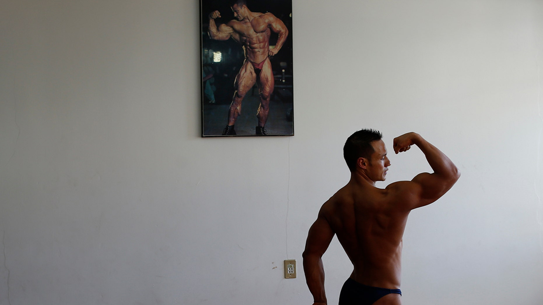 "In this June 6, 2019 photo, Carlos Suarez practices his bodybuilding poses as part of his daily training regimen ahead of the Pan Am Games, at the neighborhood gym owned by his parents in Toluca, Mexico. ""It's going to be a historic moment for my sport...It's something very beautiful, it will be a party for my sport,"" Suárez said. (AP Photo/Rebecca Blackwell)"