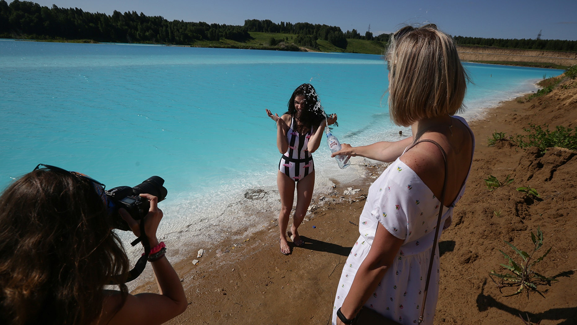 "A young woman poses for pictures by a Novosibirsk energy plant's ash dump site - nicknamed the local ""Maldives"" - on July 11, 2019. - An industrial dump site in Siberia whose turquoise lake resembles a tropical paradise has become a magnet for Instagrammers who risk their health in the toxic water to wow online followers."