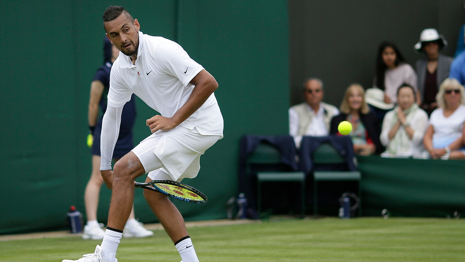 Australia's Nick Kyrgios returns the ball from between his legs to Australia's Jordan Thompson in a Men's singles match during day two of the Wimbledon Tennis Championships in London, Tuesday, July 2, 2019. (AP Photo/Tim Ireland)