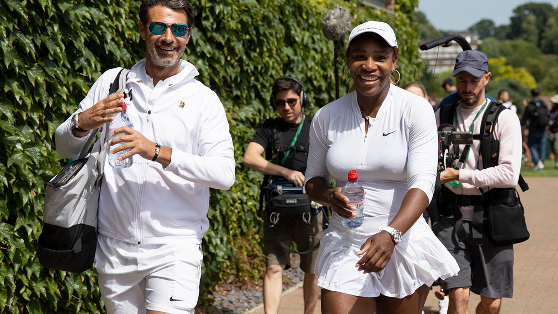 Serena Williams of USA and her coach Patrick Mouratoglou walk on after a training session at the All England Lawn Tennis Championships in Wimbledon, London, on Friday, June 28, 2019. The Wimbledon Tennis Championships 2019 will be held in London from July 1 to July 14. (Peter Klaunzer/Keystone via AP)