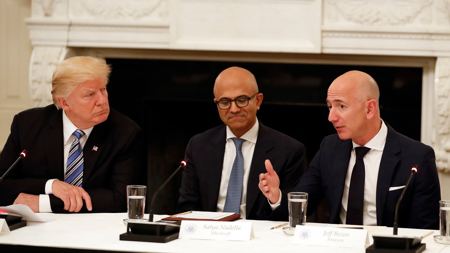 """FILE - In this Jun 19, 2017, record print President Donald Trump, left, and Satya Nadella, Chief Executive Officer of Microsoft, center, listen as Jeff Bezos, Chief Executive Officer of Amazon, speaks during an American Technology Council roundtable in a State Dinning Room of a White House in Washington. Amazon and Microsoft are battling for a $10 billion event to build a U.S. troops a initial """"war cloud."""" (AP Photo/Alex Brandon, File)"""
