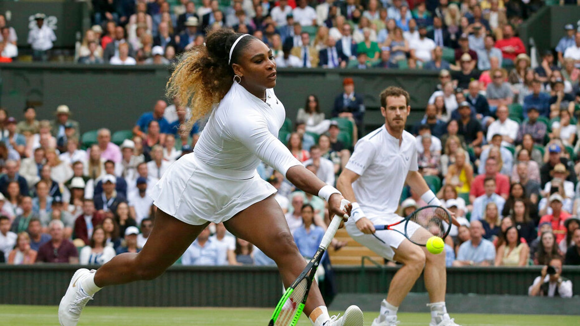 United States' Serena Williams, left, is watched by playing partner Andy Murray as she plays a shot during a mixed doubles match during day six of the Wimbledon Tennis Championships in London, Saturday, July 6, 2019. (AP Photo/Tim Ireland)