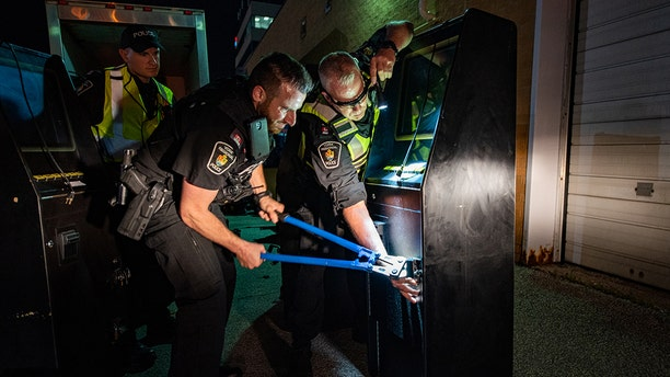 """Officers cut the locks on gambling machines seized during """"Project Sindacato"""" targeting a Mafia crime family in Ontario, Canada."""