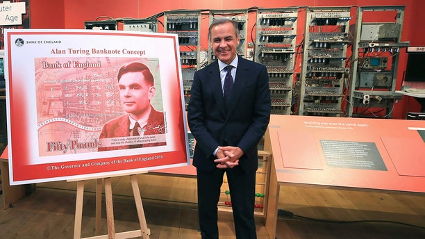 The governor of the Bank of England, Mark Carney, poses for a photo with the artwork for the concept of the new 50-pound notes, after announcing this month that the notes would honor Alan Turing. (AP)