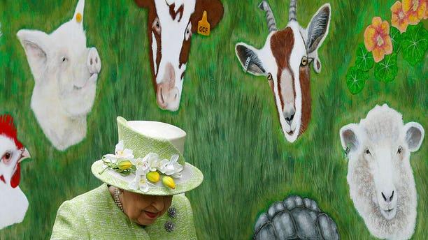Britain's Queen Elizabeth II walks by an animal mural, during a visit to Gorgie City Farm in Edinburgh, Scotland.