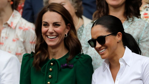 Kate, Duchess of Cambridge and Meghan, Duchess of Sussex, right, stand together during the women's singles final match on day twelve of the Wimbledon Tennis Championships in London, July 13, 2019. (AP Photo/Ben Curtis)