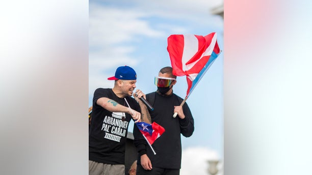 Puerto Rican rapper Rene Juan Perez known by his stage name of Residente, left, speaks to the crowd in front of the Puerto Rican Capitol in San Juan Wednesday (AP Photo/Dennis M. Rivera Pichardo)