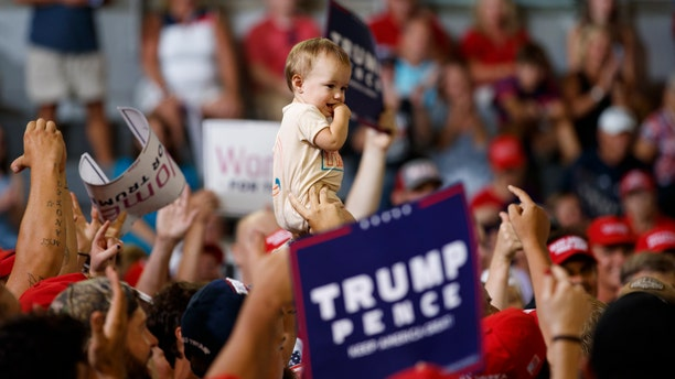 A baby is held high in the audience as President Donald Trump speaks at a campaign rally at Williams Arena in Greenville, N.C., Wednesday, July 17, 2019. (AP Photo/Carolyn Kaster)
