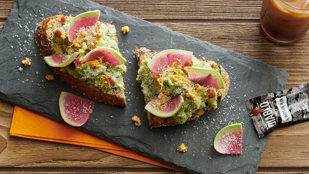 Avocado Toast-ada, served on local multigrain toast with avocado, breakfast radish, chipotle seasoned sorghum and diablo puffs.