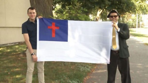 Nathaniel Shurtleff, counselor,and Tom Moor, instructor, for Camp Constitution hold the Christian flag, which was not allowed to fly by the city of Boston in 2017 and 2018. Now the group is suing the city for religious discrimination.