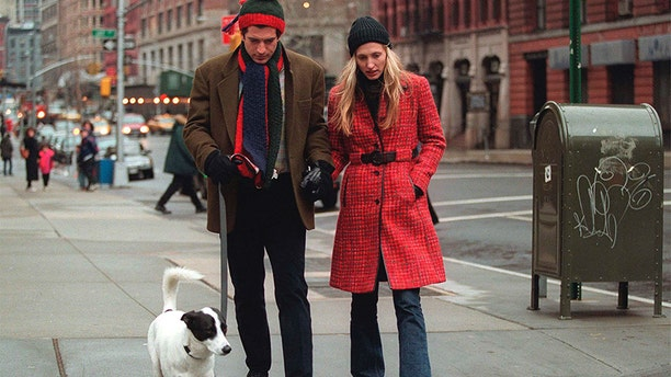 John F. Kennedy Jr. and his wife, Carolyn, walk with their dog January 1, 1997, in New York City.