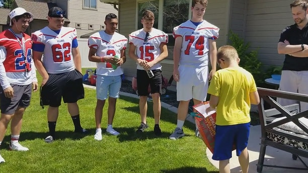 Christian Larsen opened a gift fromNampa High School Football playerswho attended his birthday party.