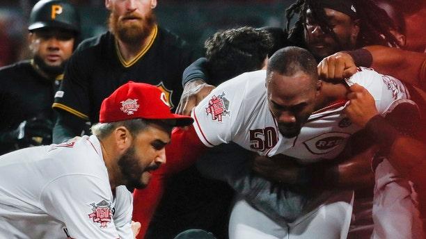 Pittsburgh Pirates' Kyle Crick (30) falls between Cincinnati Reds' Eugenio Suarez, left, and Amir Garrett (50) during a brawl in the ninth inning of a baseball game Tuesday, July 30, 2019, in Cincinnati. (AP Photo/John Minchillo)