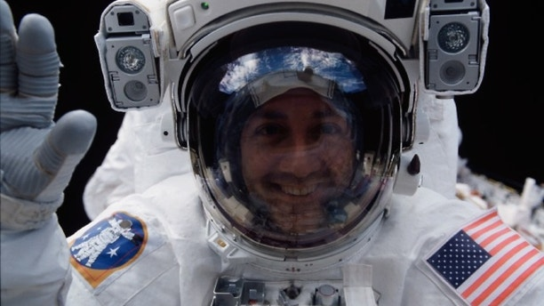 Astronaut Mike Massimino peers into space shuttle Columbia's crew cabin during a brief break in work on the Hubble Space Telescope on March 5, 2002.