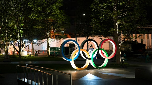 In this June 23, 2019, photo, a security officer uses a flashlight to check on the Olympic Rings in front of the New National Stadium in Tokyo. Overwhelmed by unprecedented demand, Tokyo Olympic organizers said Thursday they would run another ticket lottery next month for residents of Japan to view the games. Millions of Japanese were let down last month when they came away empty-handed without tickets for next year's Olympics. (AP Photo/Jae C. Hong)