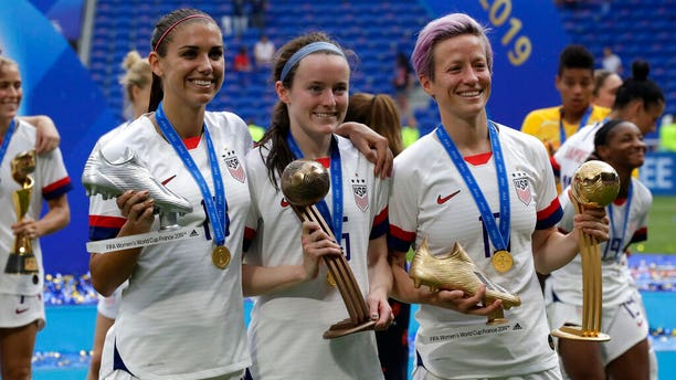 United States' Megan Rapinoe, right, United States' Alex Morgan, left, and United States' Rose Lavelle, center, pose with their trophies after the Women's World Cup final soccer match between US and The Netherlands. (AP Photo/Alessandra Tarantino)