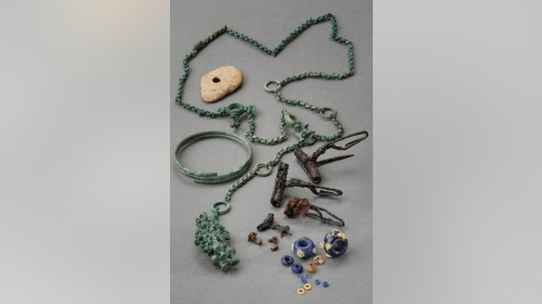 Restored found objects, including a belt chain, bracelet, brooches, glass and amber beads. (Credit: Martin Bachmann, Kantonsarchäologie Zürich)