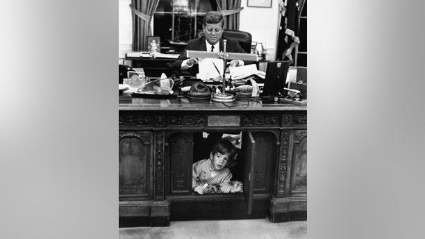 John F. Kennedy Jr. exploring his father's desk. — Getty