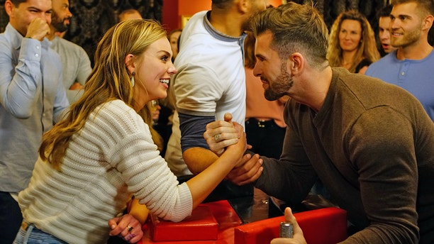 """""""The Bachelorette"""" star Hannah Brown arm wrestles with contestant Jed Wyatt. Wyatt came under fire for allegedly having a girlfriend before leaving Nashville to film the reality series."""