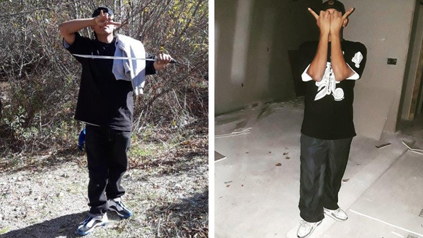 Prosecutors say photos show MS-13 gang member standing in the woods holding a machete and flashing a gang sign and flashing a gang sign