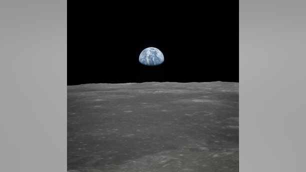 """This view of Earth rising over the moon's horizon was taken from the Apollo spacecraft. The lunar terrain pictured is in the area of Smyth's Sea on the nearside. Coordinates of the center of the terrain are 85 degrees east longitude and 3 degrees north latitude. While astronaut Neil A. Armstrong, commander; and Edwin E. Aldrin Jr., lunar module pilot, descended in the Lunar Module (LM) """"Eagle"""" to explore the Sea of Tranquility region of the moon, astronaut Michael Collins remained with the Command and Service Modules (CSM) """"Columbia"""" in lunar orbit. (Credit: NASA)"""