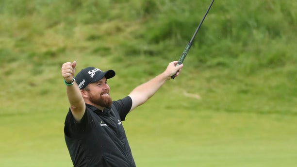 Ireland's Shane Lowry lifts his club to celebrate as he wins the British Open Golf Championships at Royal Portrush in Northern Ireland, Sunday, July 21, 2019.