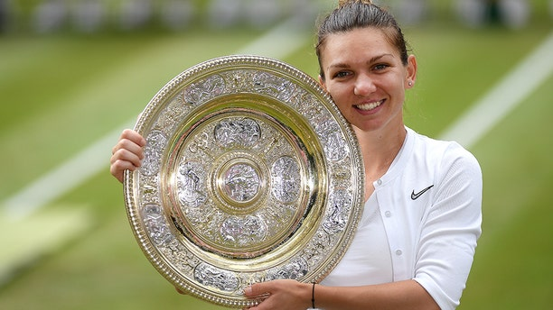 Simona Halep of Romania pose for a photo with her trophy after winning the Ladies' Singles final against Serena Williams of The United States during Day twelve of The Championships - Wimbledon 2019 at All England Lawn Tennis and Croquet Club on July 13, 2019 in London, England. (Photo by Mike Hewitt/Getty Images)