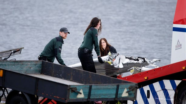 Emergency personnel move a part of a wing and other plane wreckage retrieved from the crash site at Ume river outside Umea, Sweden, on Monday July 15, 2019.