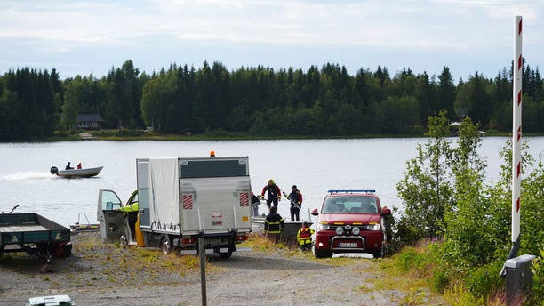 Emergency services attend the accident site at a small harbor at Ume river, outside Umea, Sweden, Sunday July 14, 2019.