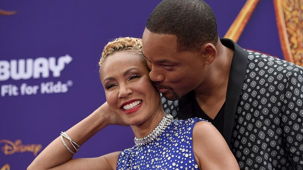 "Will Smith, right, kisses Jada Pinkett Smith as they arrive at the premiere of ""Aladdin"" at the El Capitan Theatre in Los Angeles."
