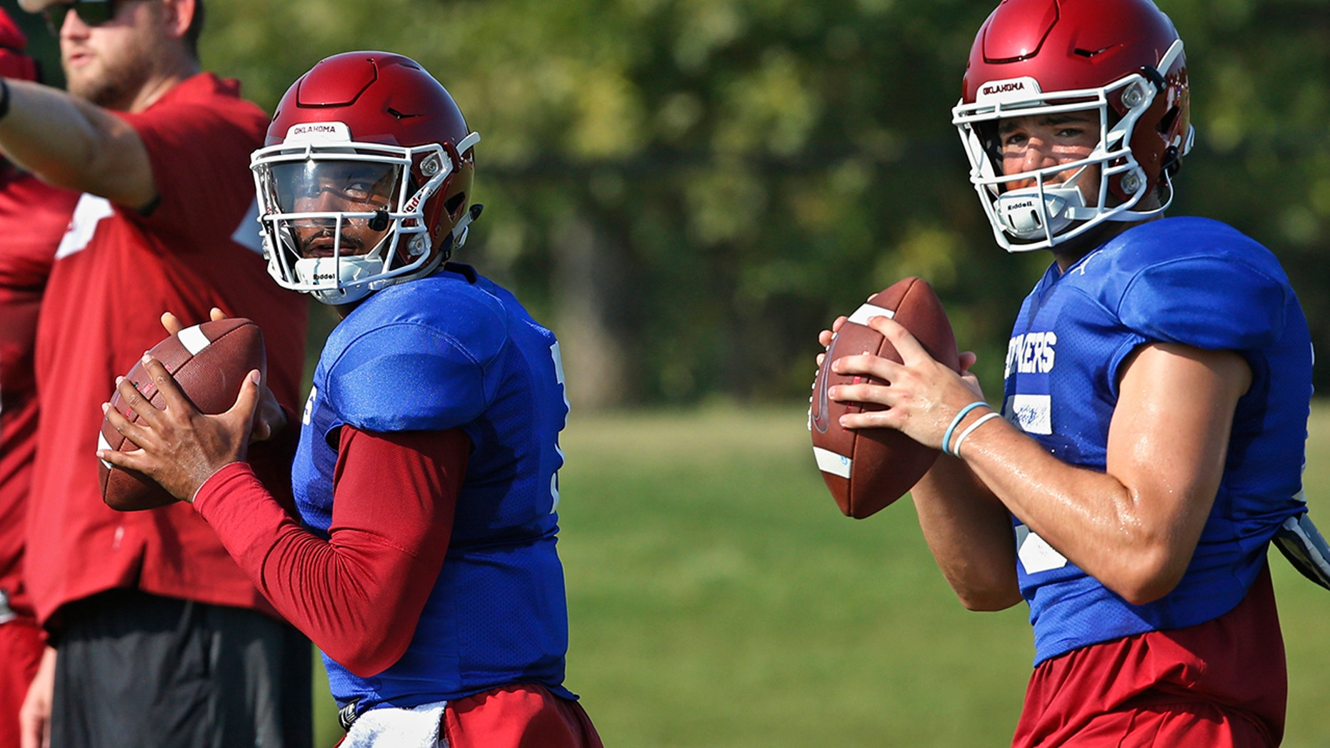 FILE - In this Monday, Aug. 5, 2019, file photo, Oklahoma quarterbacks Jalen Hurts, left, and Tanner Mordecai, right, throw during NCAA college football practice in Norman, Okla. Hurts is competing with Mordecai, a redshirt freshman, and Spencer Rattler, a true freshman, to become starting quarterback. (AP Photo/Sue Ogrocki, File)
