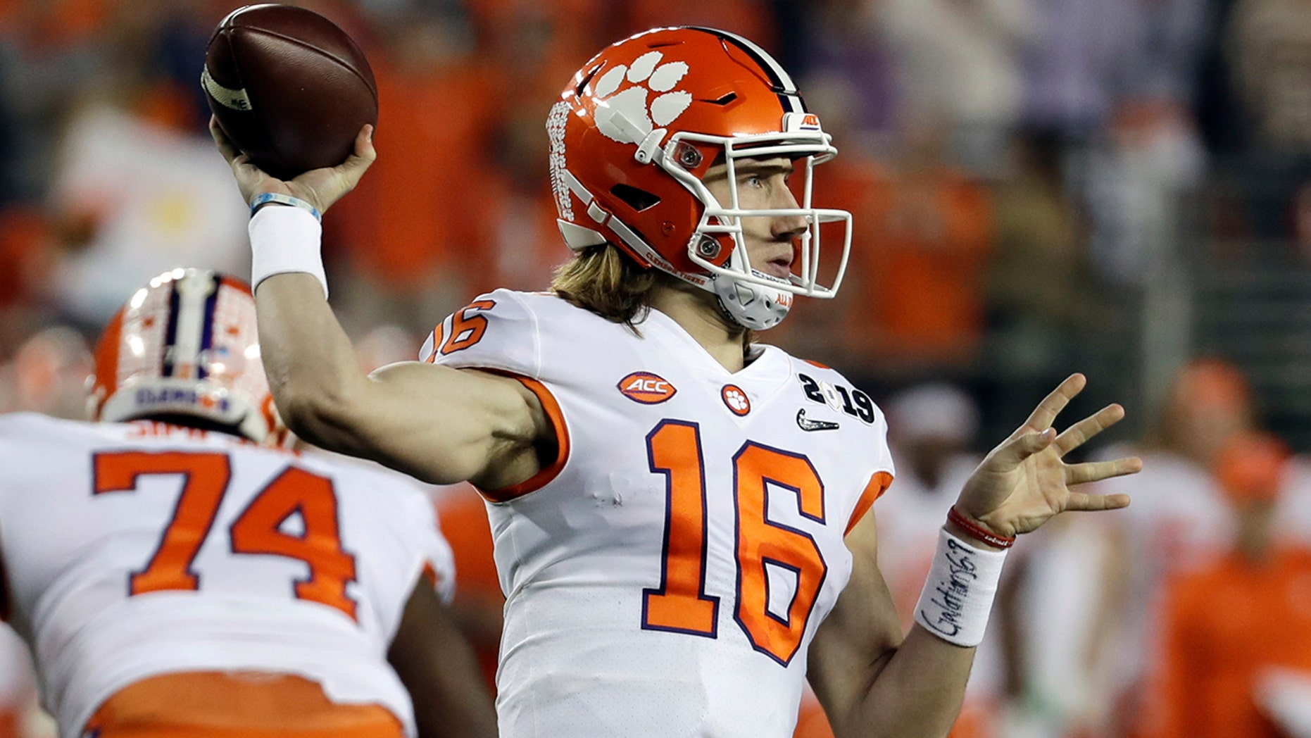 "FILE - In this Jan. 7, 2019, file photo, Clemson's Trevor Lawrence throws during the first half the NCAA college football playoff championship game against Alabama, in Santa Clara, Calif. Sure, Clemson lost all four of its ""Power Rangers"" defensive line and seven starters on defense from its title team. But the Tigers' offense, led by Heisman Trophy candidates quarterback Trevor Lawrence and tailback Travis Etienne, looks ready to operate at an even higher level than a year ago when it averaged 527 yards and 44.3 points a game. (AP Photo/Chris Carlson, File)"