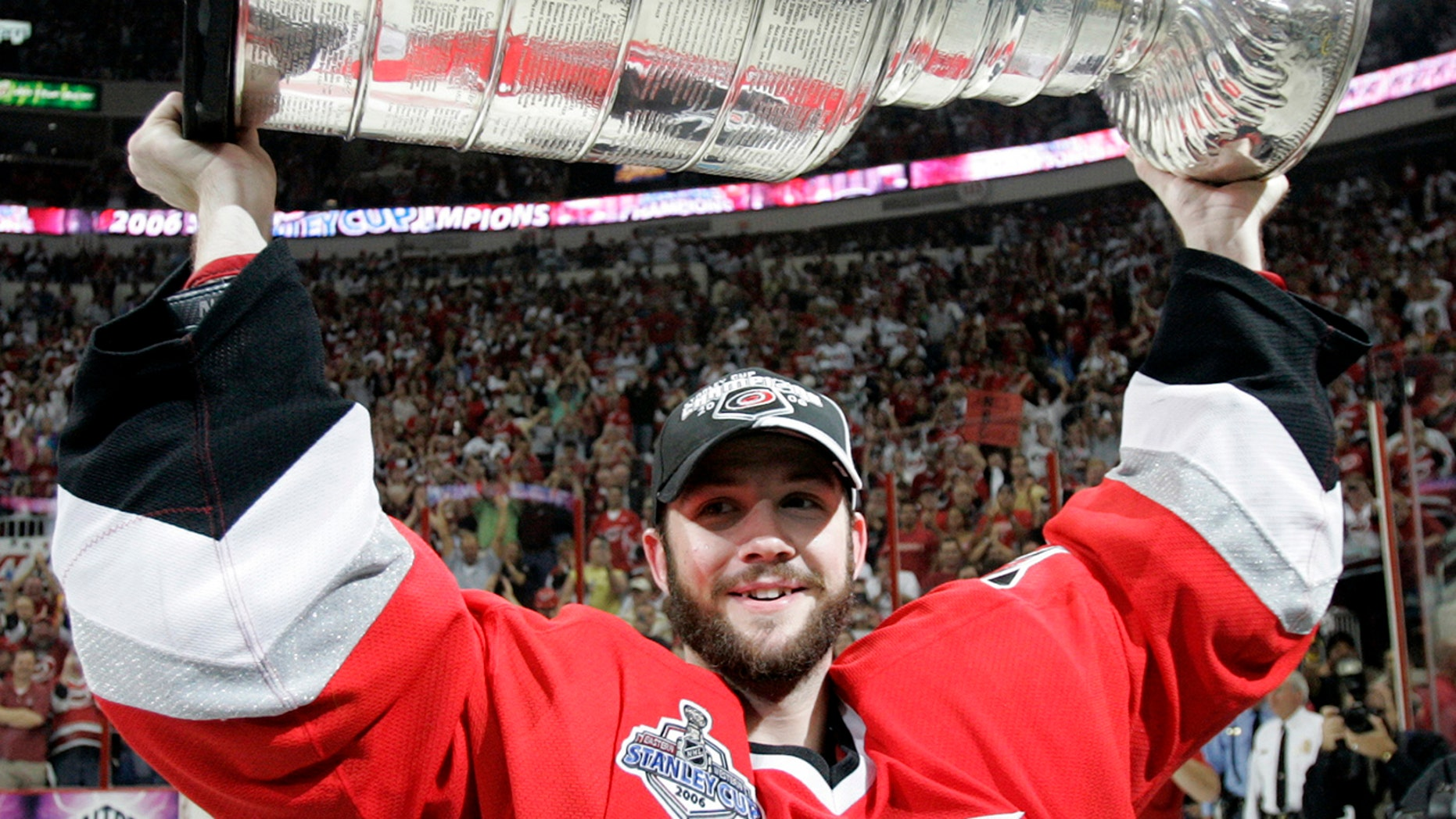 """FILE - In this June 19, 2006, file photo, Carolina Hurricanes goaltender Cam Ward hoists the Stanley Cup after the Hurricanes defeated the Edmonton Oilers 3-1 in Game 7 of the Stanley Cup hockey finals in Raleigh, N.C. Goalie Cam Ward has signed a one-day contract with the Carolina Hurricanes and is retiring as a member of the team he helped lead to a Stanley Cup. General manager Don Waddell announced the signing and retirement Wednesday, Aug. 28, 2019, calling Ward """"a cornerstone for this organization for more than a decade.""""(AP Photo/Ann Heisenfelt, File)"""