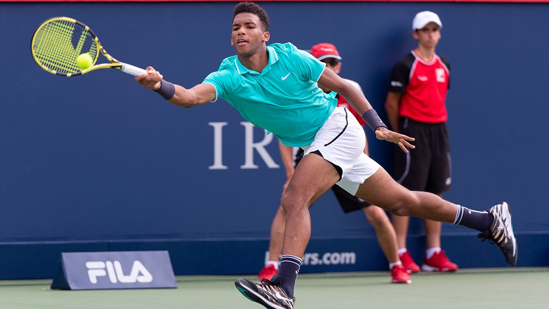 Felix Auger-Aliassime of Canada lunges to return to compatriot Vasek Pospisil during a first round match at the Rogers Cup tennis tournament in Montreal, Tuesday, Aug. 6, 2019. (Paul Chiasson/The Canadian Press via AP)