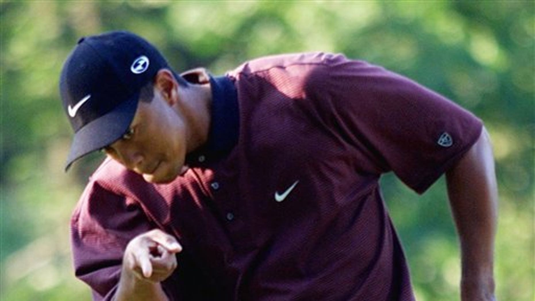 FILE - In this Aug. 20, 2000 file photo, Tiger Woods points to his ball as it drops for birdie on the first hole of a three-hole playoff against Bob May at the PGA Championship at the Valhalla Golf Club in Louisville, Ky. On his web site Friday night, Dec. 11, 2009, Woods announced that he is taking an indefinite break from professional golf. (AP Photo/Chuck Burton, File)