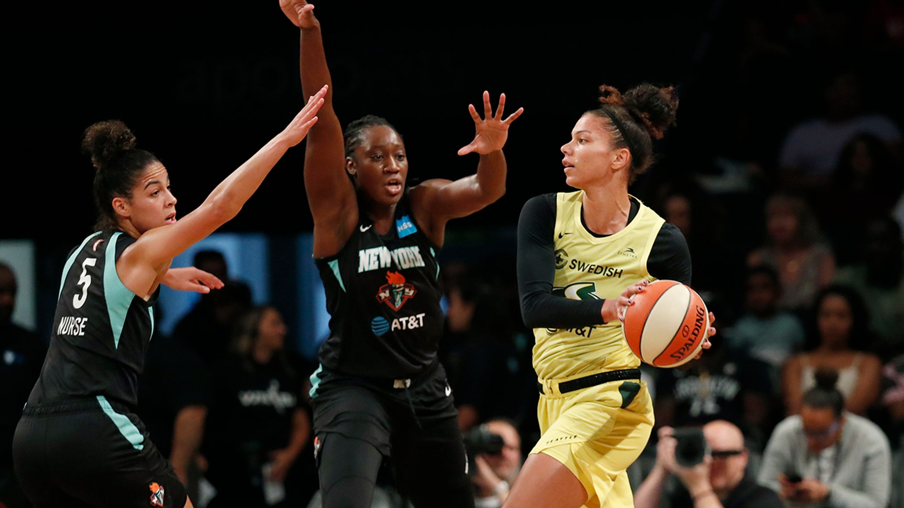 Seattle Storm forward Alysha Clark, right, passes as New York Liberty guard Kia Nurse, left, and center Tina Charles,center, defend during the first half of a WNBA basketball game, Sunday, Aug. 11, 2019, in New York. (AP Photo/Kathy Willens)