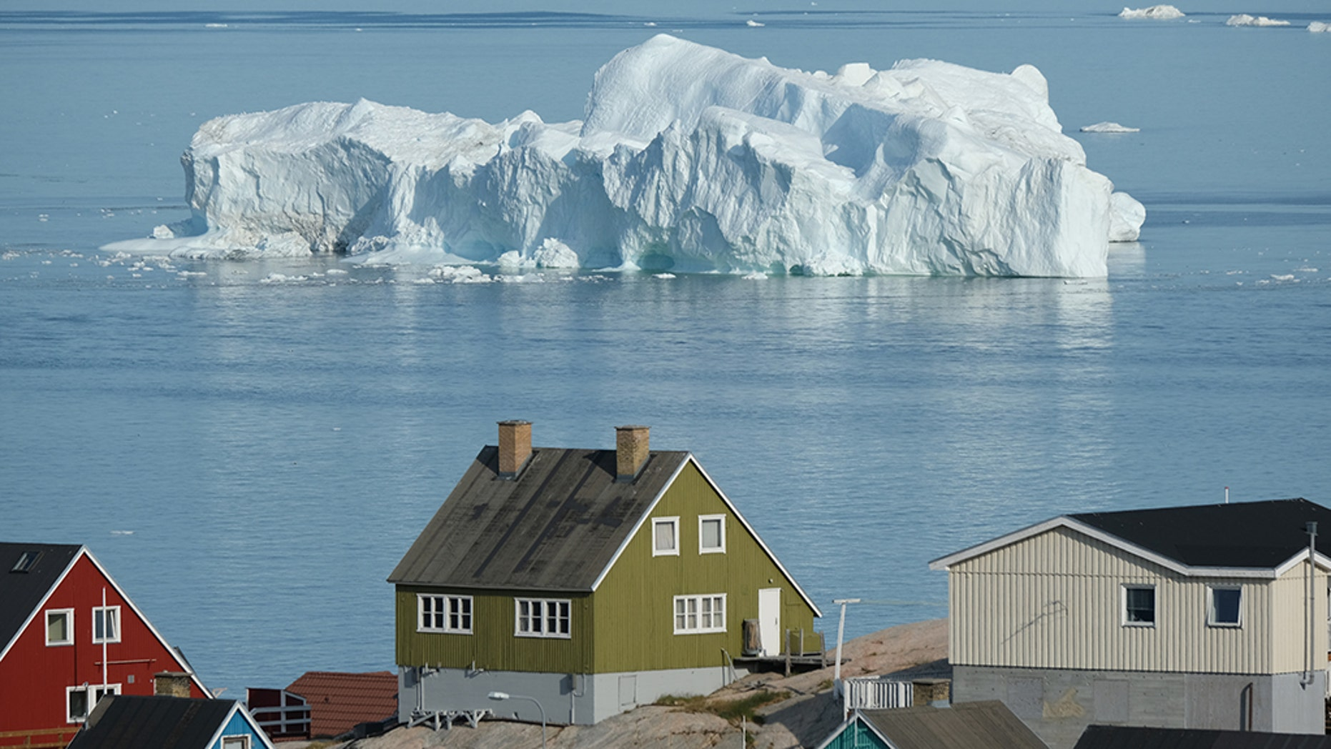 An iceberg floats in Disko Bay behind houses during unseasonably warm weather on July 30, 2019 in Ilulissat, Greenland. (Photo by Sean Gallup/Getty Images)