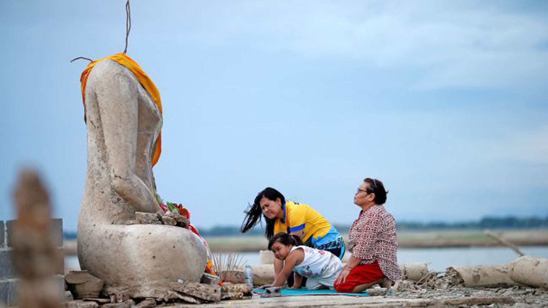 A family prays near the ruins of a headless Buddha statue that resurfaced in a dried-up dam because of a drought in Lopburi, Thailand, on Aug. 1, 2019. (Credit: Soe Zeya Tun/Reuters/Newscom)