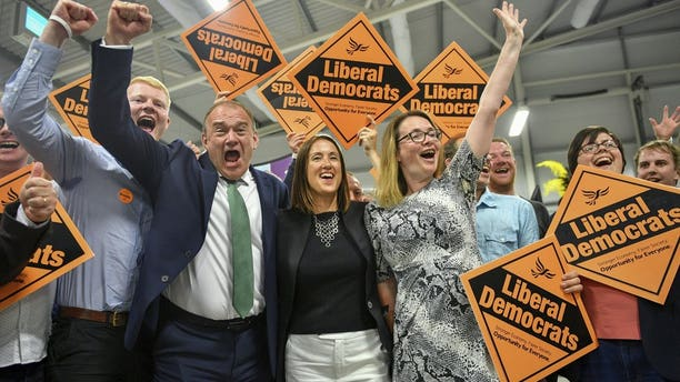 Liberal Democrats' Jane Dodds, centre, celebrates with supporters as she wins the seat in the Brecon and Radnorshire by-election at the Royal Welsh Showground in Llanelwedd, Builth Wells, Wales Friday, Aug. 2, 2019. After a first week in office that saw him booed in Scotland and berated in Belfast, British Prime Minister Boris Johnson was facing his first electoral test on Thursday, a special election that could see his Conservative government's working majority in Parliament cut to just one vote.