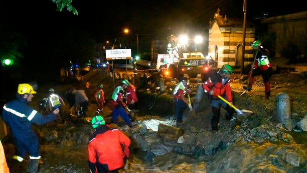 Rescuers work to clear mud from a road in Codesino, near the northern Italian town of Lecco, in the early hours of Wednesday, Aug. 7.