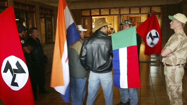 """Supporters of the Afrikaner Resistance Movement (AWB) display an old South African flag, second from left, an old Afrikaner """"Vierkleur"""" flag and swastika-like flags as they await the release of their leader, Eugene Terre'Blanche from prison in Potchefstroom, South Africa where he was granted parole after serving three years of an effective five year sentence for the 1996 attempted murder of a black security guard."""