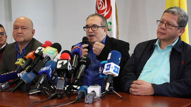 Flanked by Carlos Lozada, left, and Pablo Catatumbo, right, Rodrigo Londono who had been the Revolutionary Armed Forces of Colombia, FARC, top military commander and now heads its legal political party, speaks during a press conference in Bogota, Colombia, Thursday, Aug. 29, 2019.