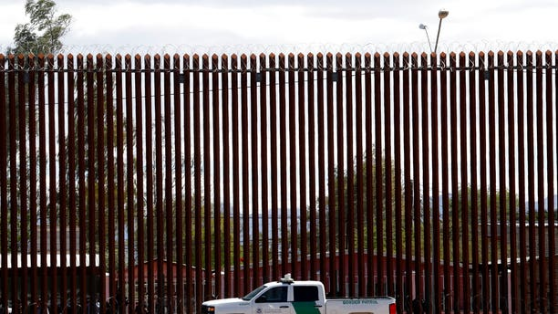 A Customs and Border Protection vehicle sits near the wall as President Trump visits a new section of the border wall with Mexico in El Centro, Calif.